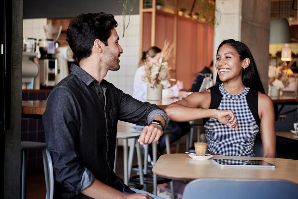 Two friends greeting each other in a cafe